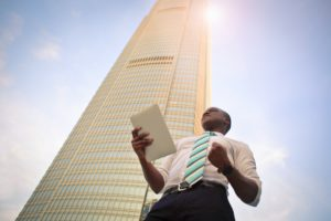 Young Man standing under tall building
